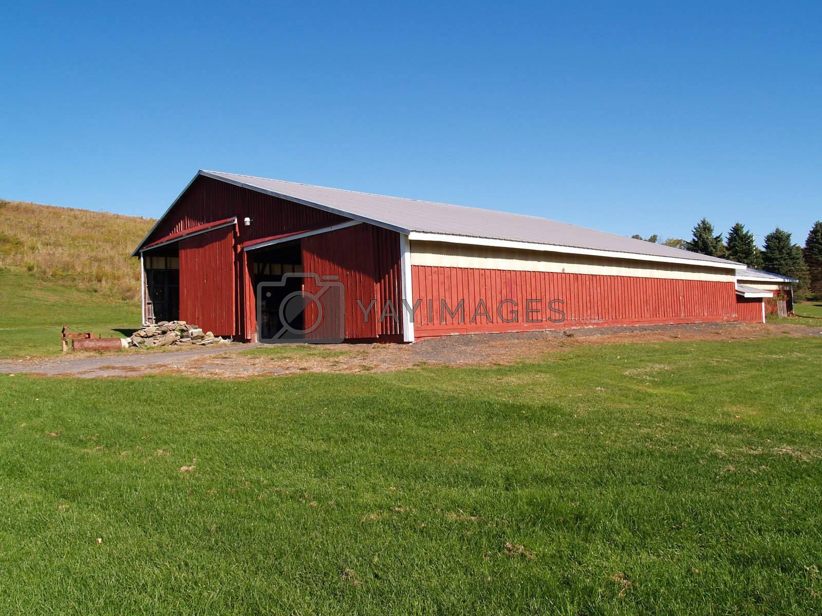 view of a large red barn in the country