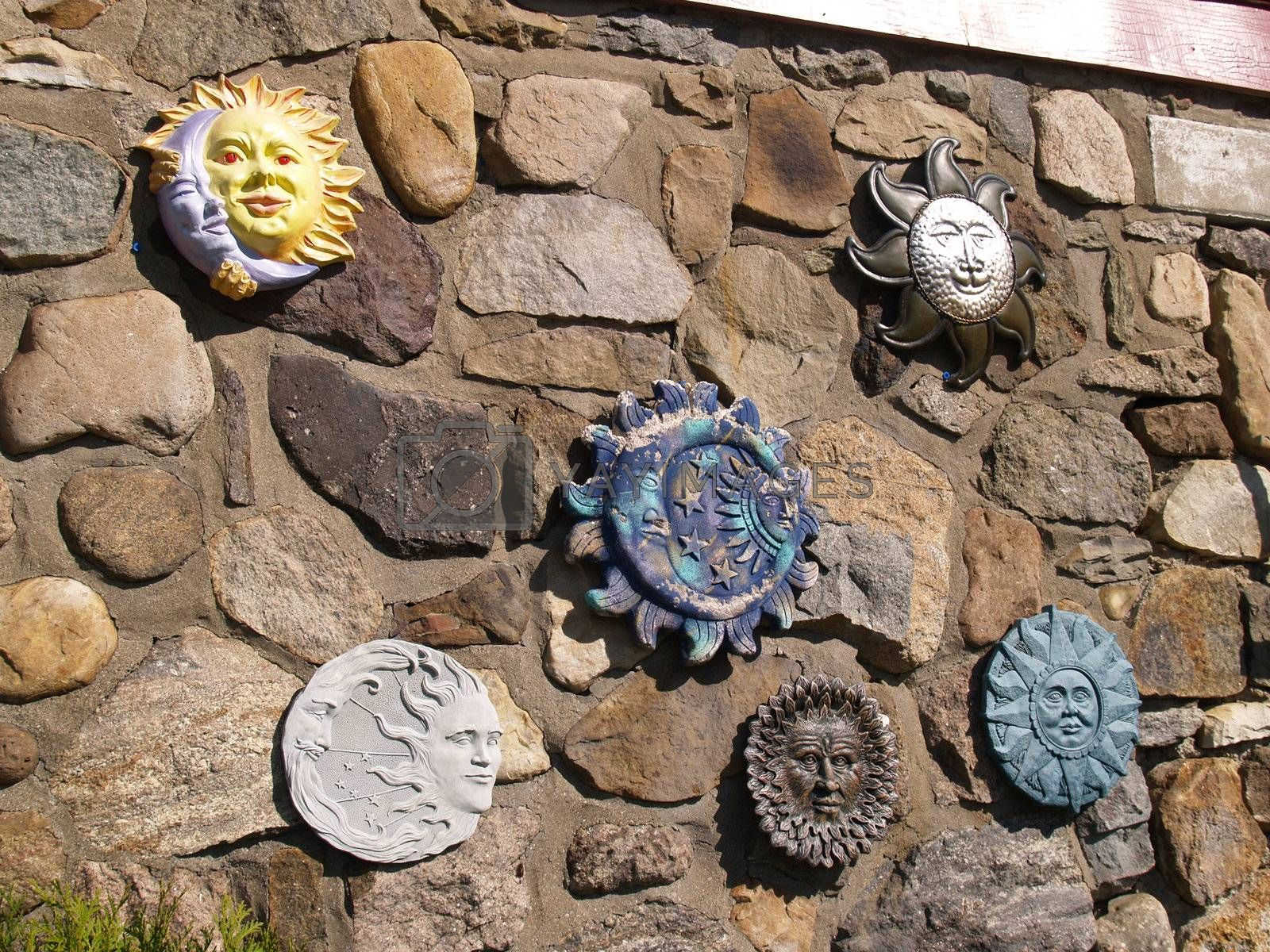 many celestial sun and moons on a stone wall
