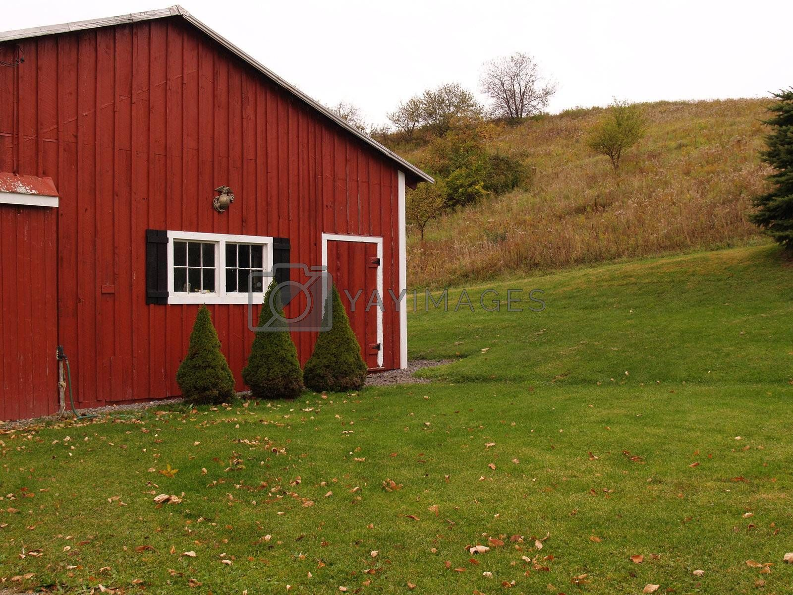 red outdoor utility building by grass and a hill