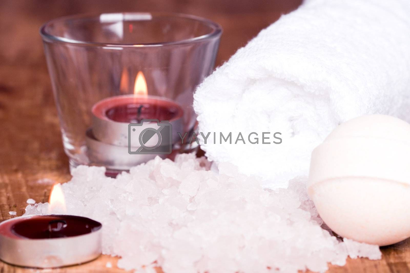 spa products (towel, salt, candles, ball) on wooden background