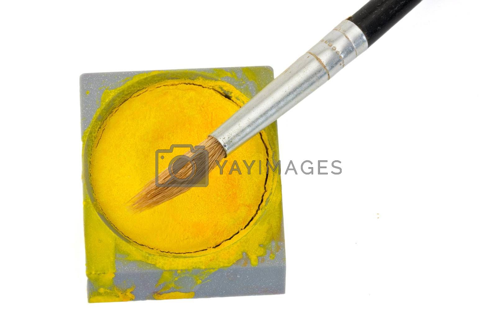 a brush and a yellow watercolor tin isolated on white
