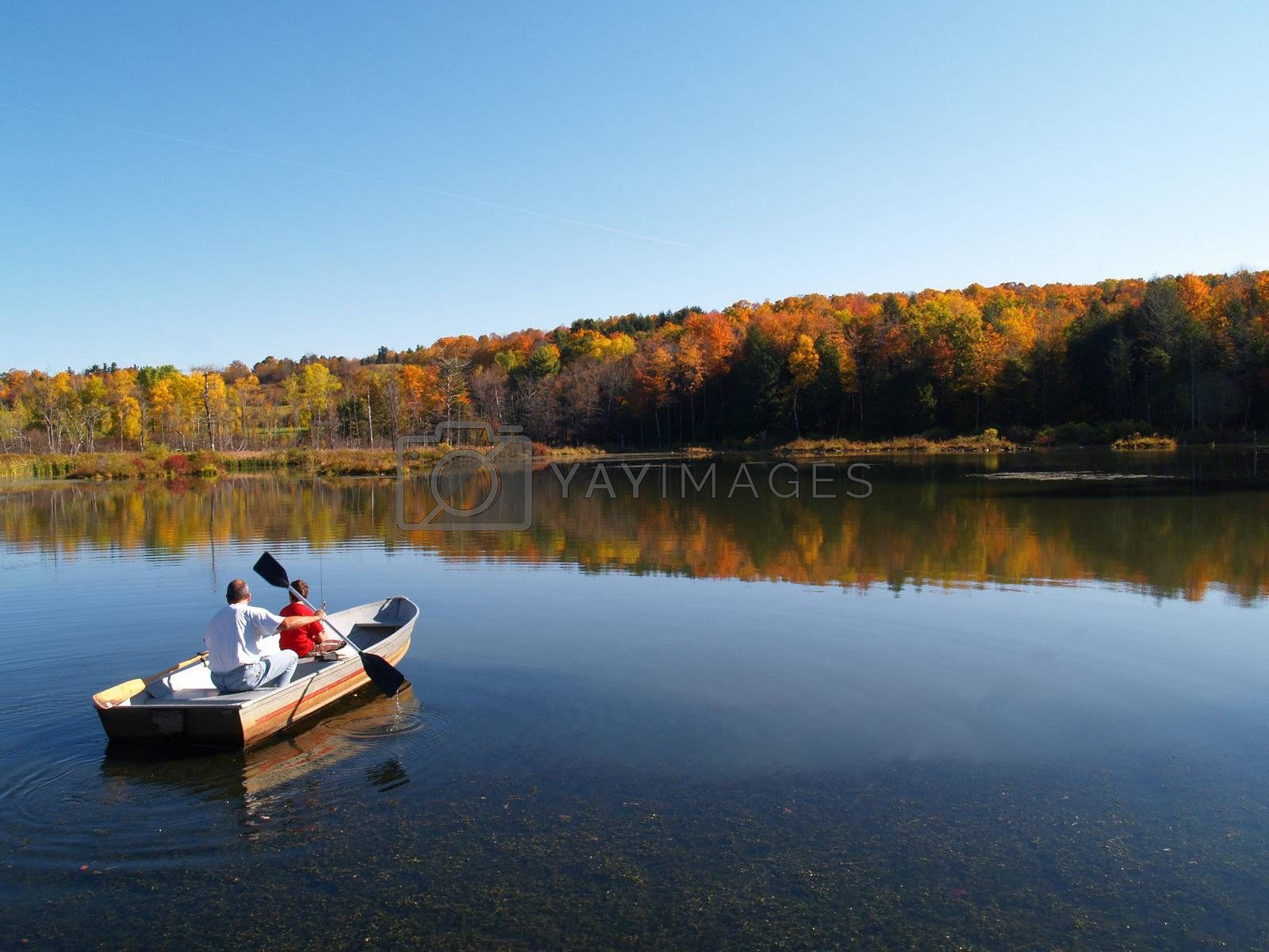 father and son fishing in autumn on  a calm lake