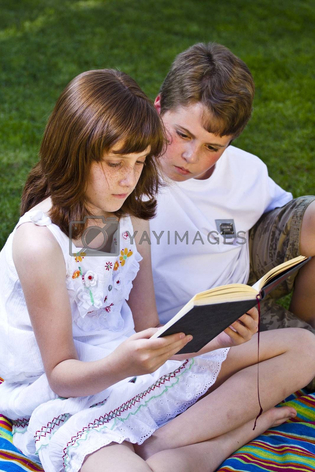 Portrait of cute kids reading books  in natural environment