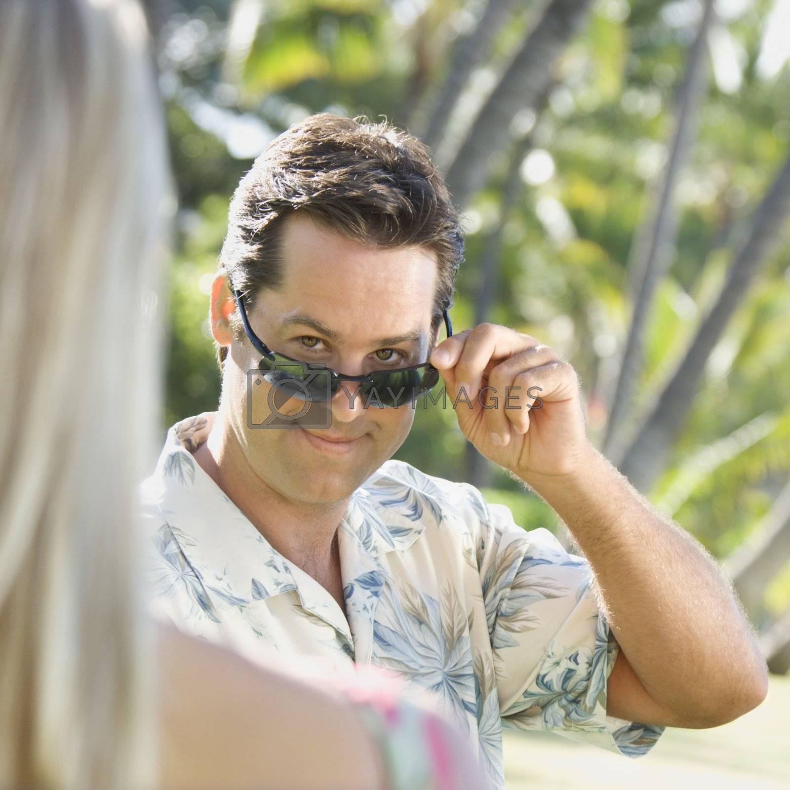 Caucasian mid adult man tilting sunglasses at woman.