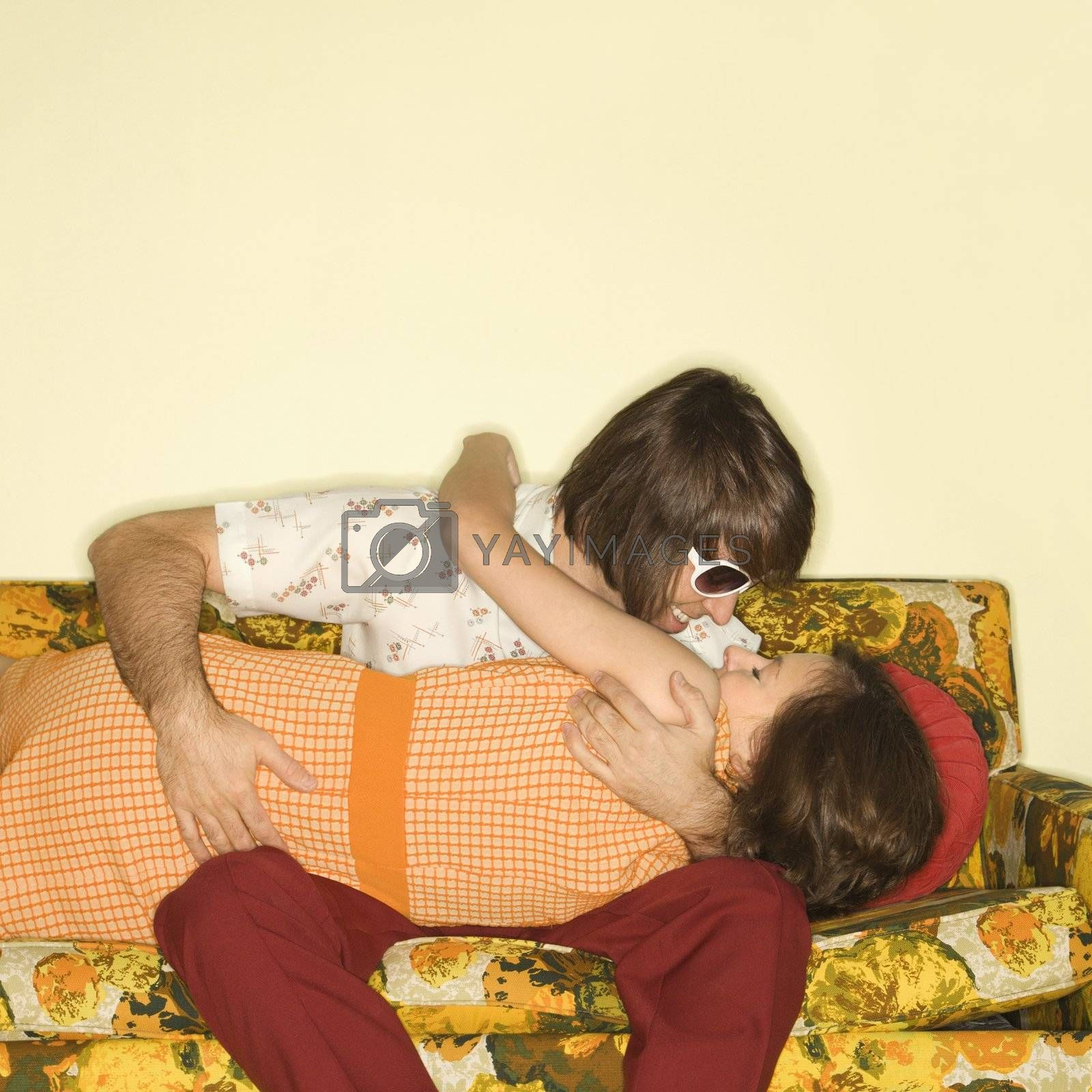 Caucasian mid-adult couple smiling and embracing on colorful retro sofa.