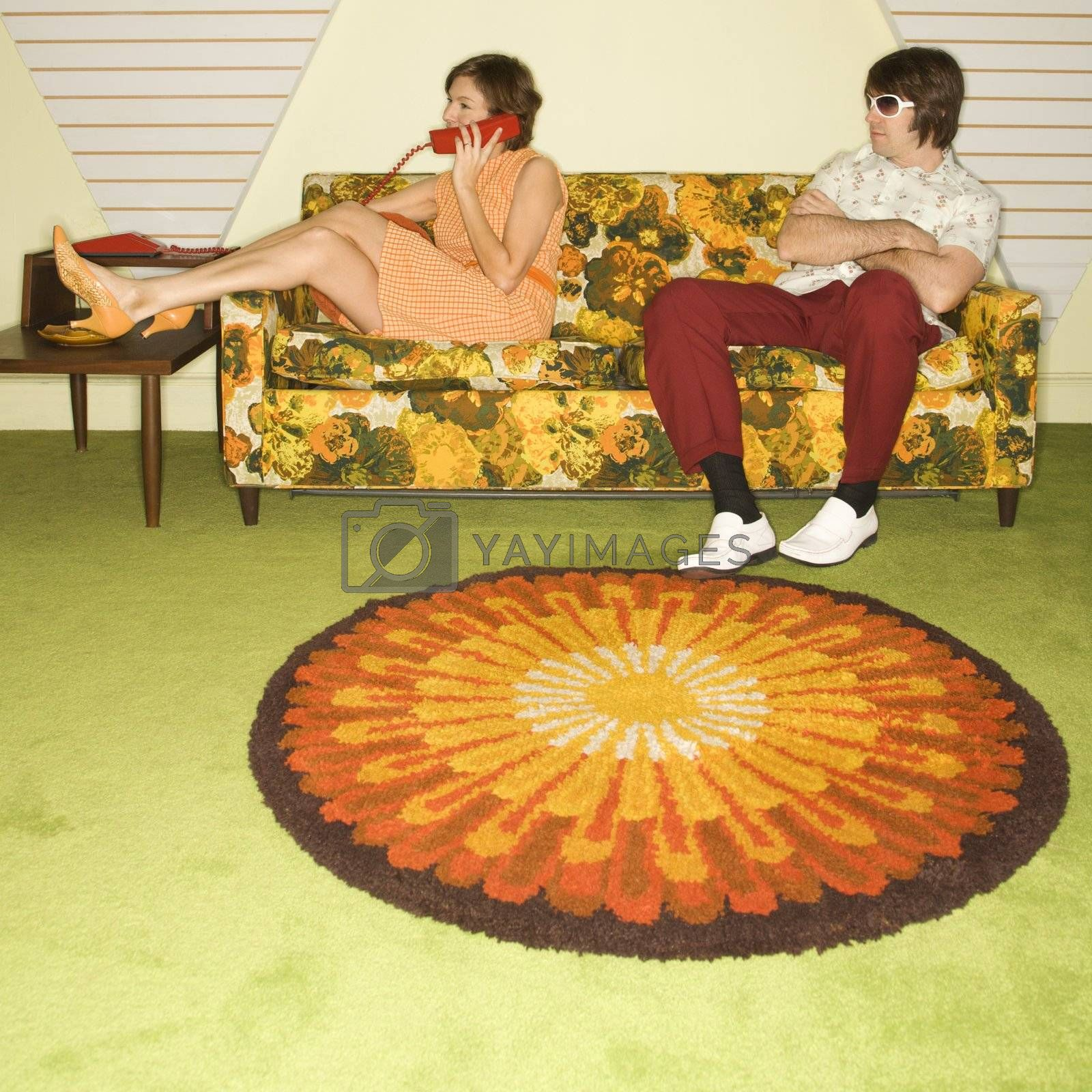 Caucasian mid-adult woman on phone while Caucasian mid-adult man wearing sunglasses watches from sofa.
