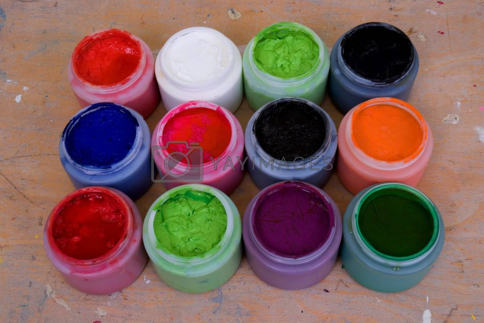 Twelve tubs of acrylic paint on a work bench