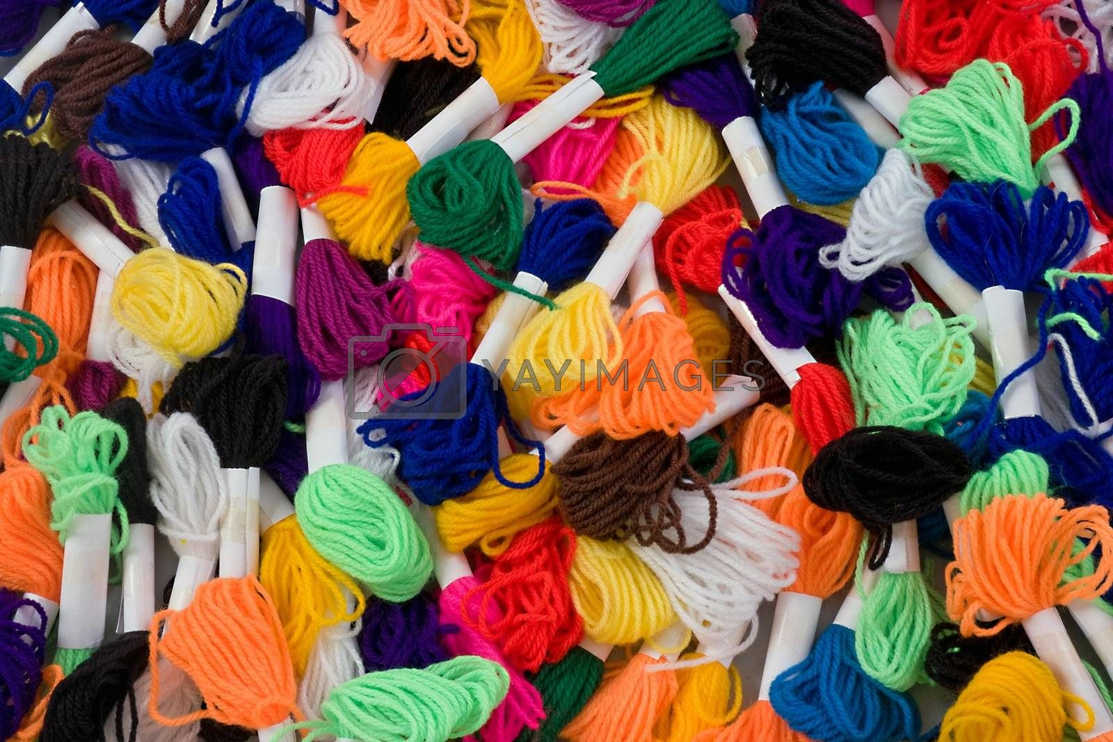 Many coloured samples of wool as a background