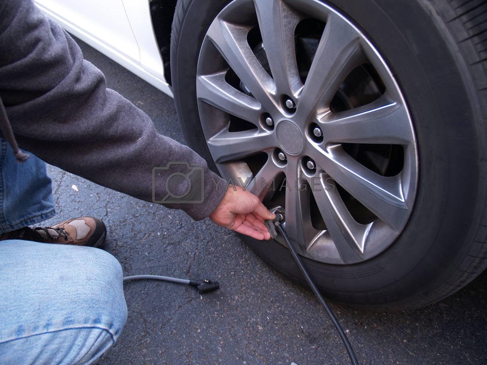 man checking air pressure in car tire
