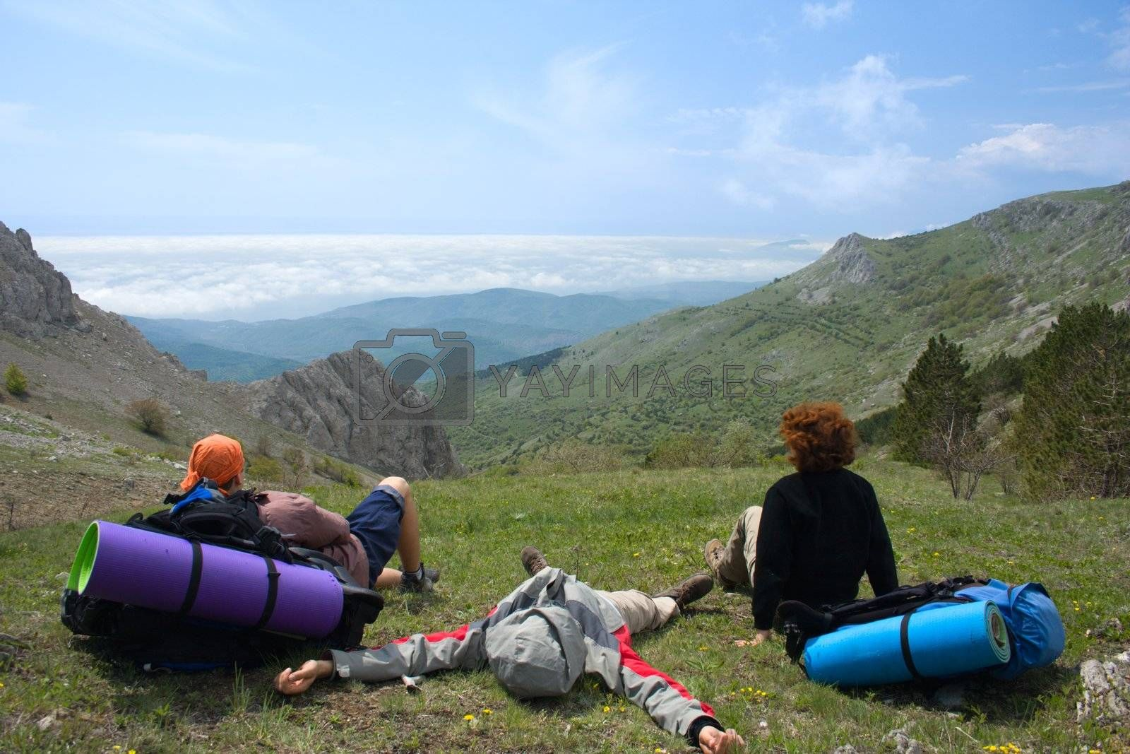Backpackers relaxing on pass and looking to clouds