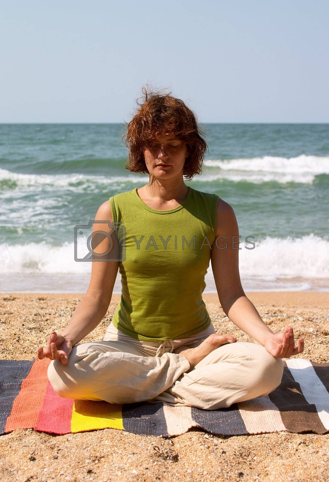 girl meditating in yoga pose padmasana on the seaside