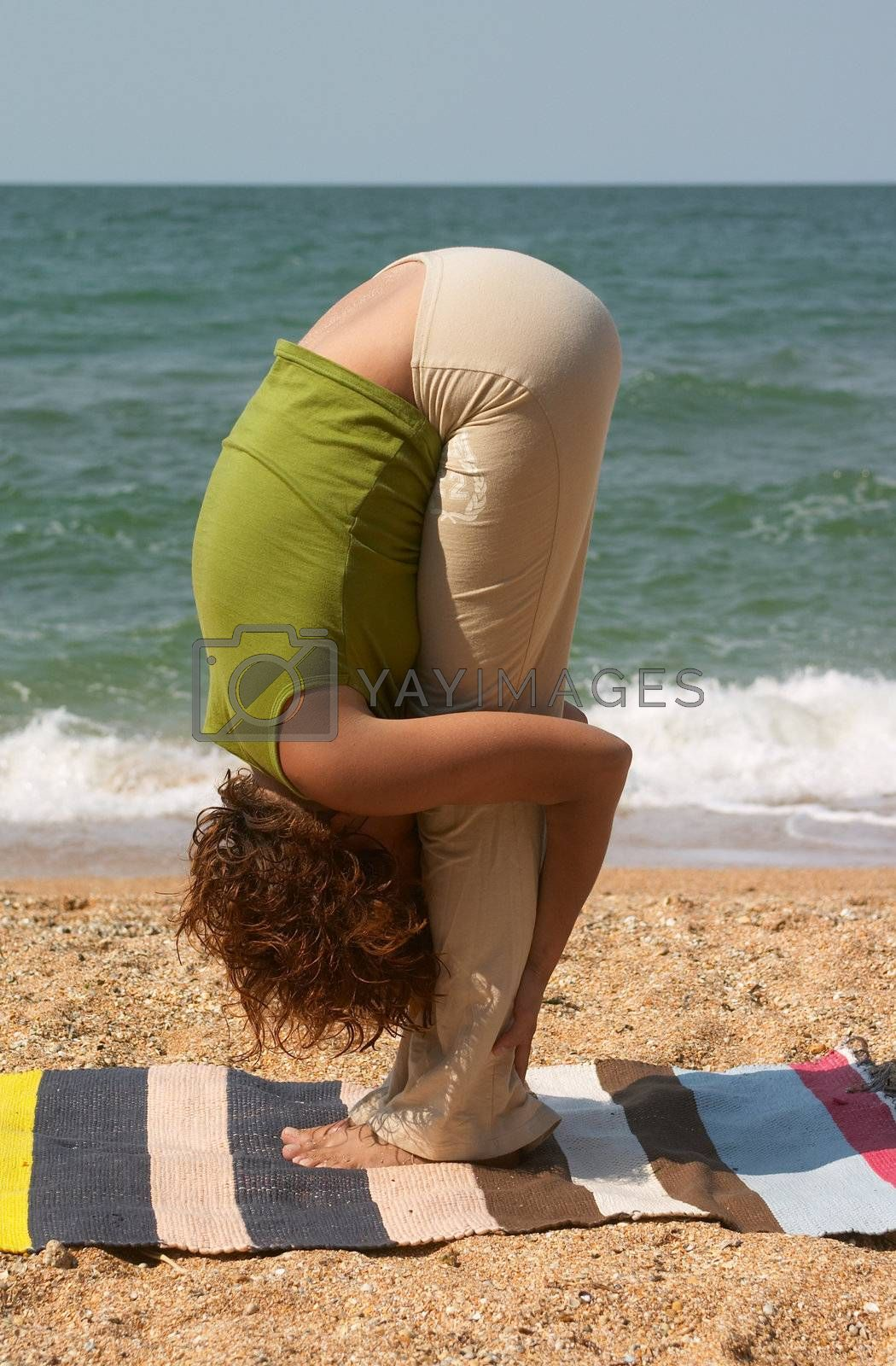 girl doing Uttanasana yoga pose at sea coast