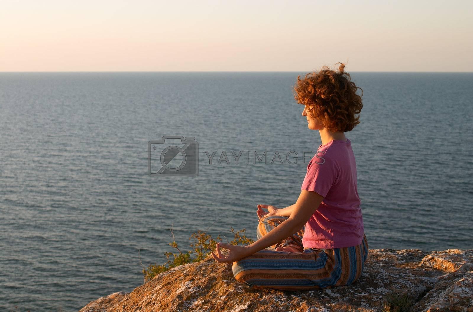 girl meditating on the cliff in padmasana pose