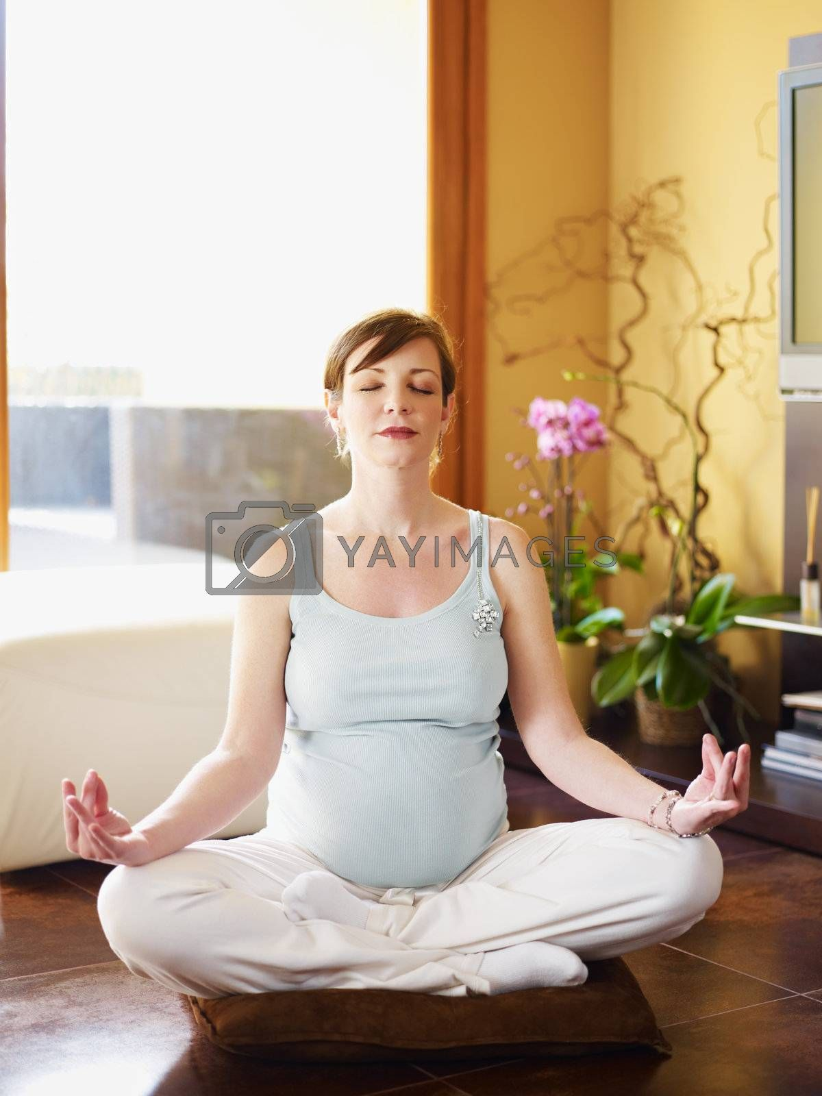 italian 6 months pregnant woman sitting with crossed legs doing yoga exercise at home. Vertical shape; full length, front view. Copy space