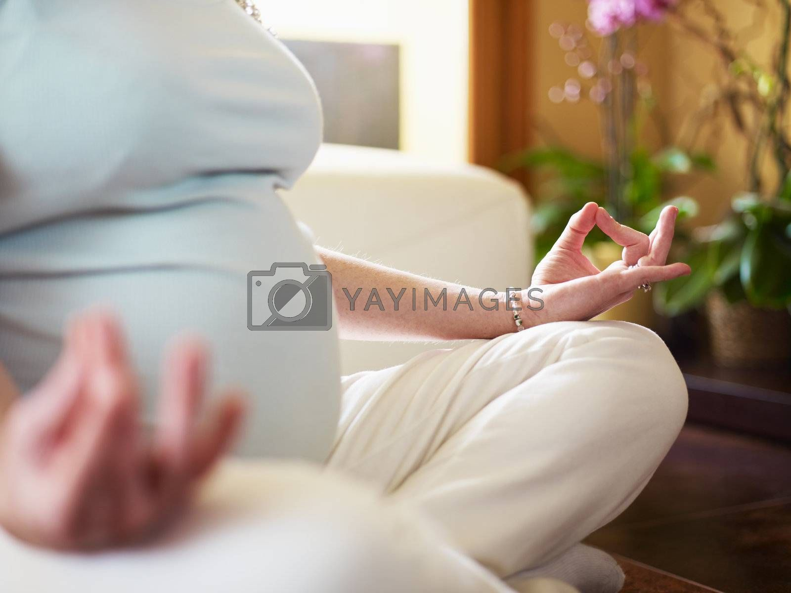 cropped view of italian 6 months pregnant woman sitting with crossed legs doing yoga exercise at home. Horizontal shape, narrow focus