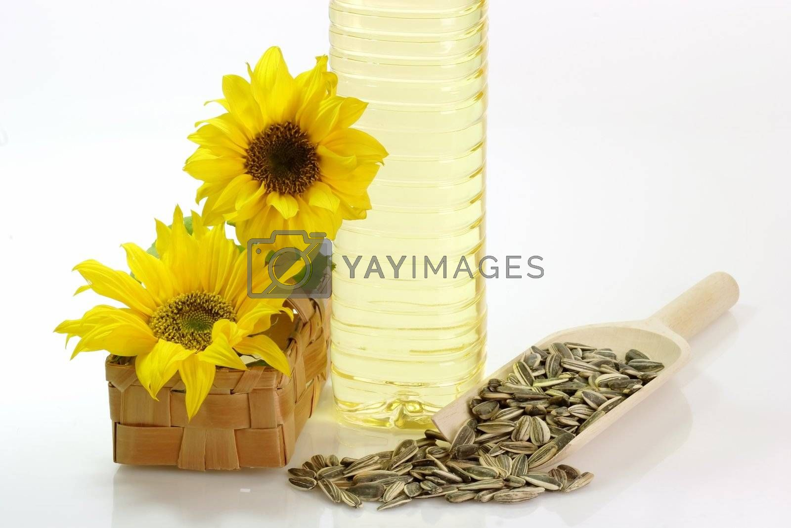 Cooking oil in a plastic bottle with sunflower seeds on white background