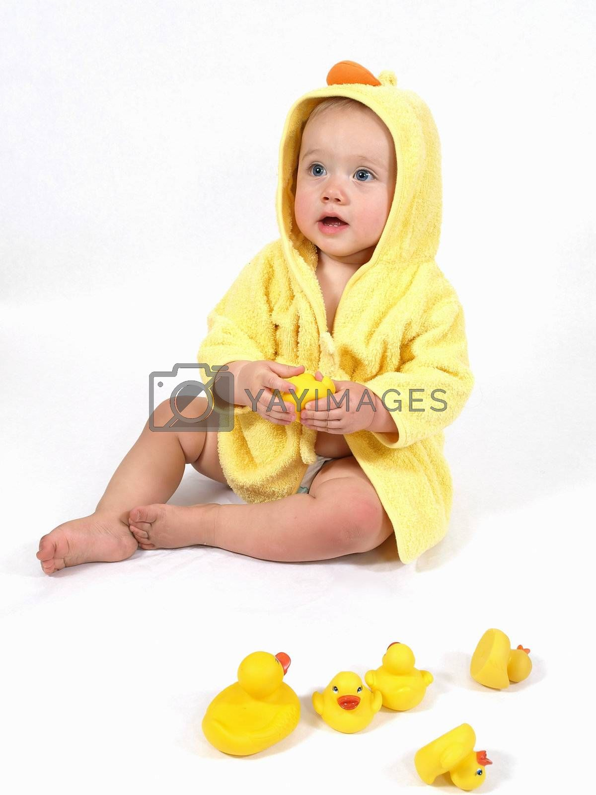 A baby girl in a yellow duck bathrobe holds a plastic toy rubber duck.