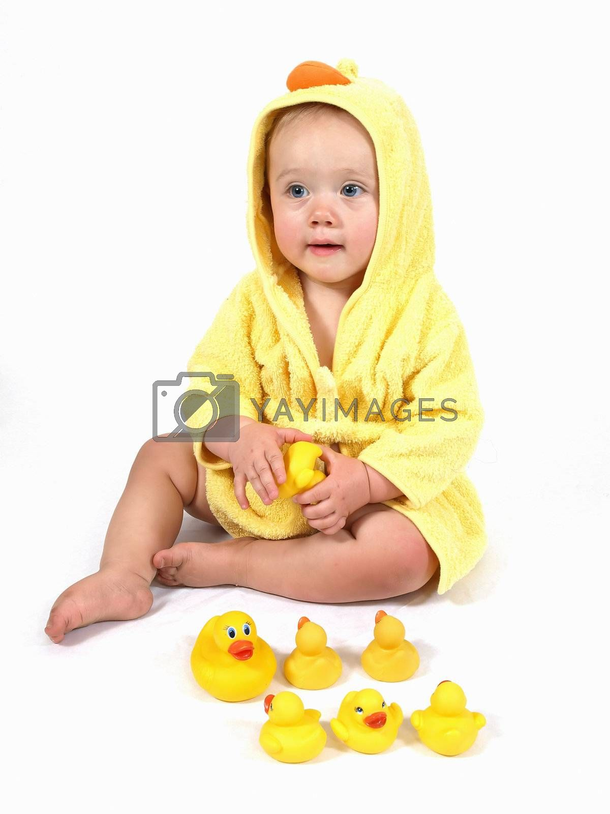A female child wearing a yellow bathrobe plays with her rubber ducks.