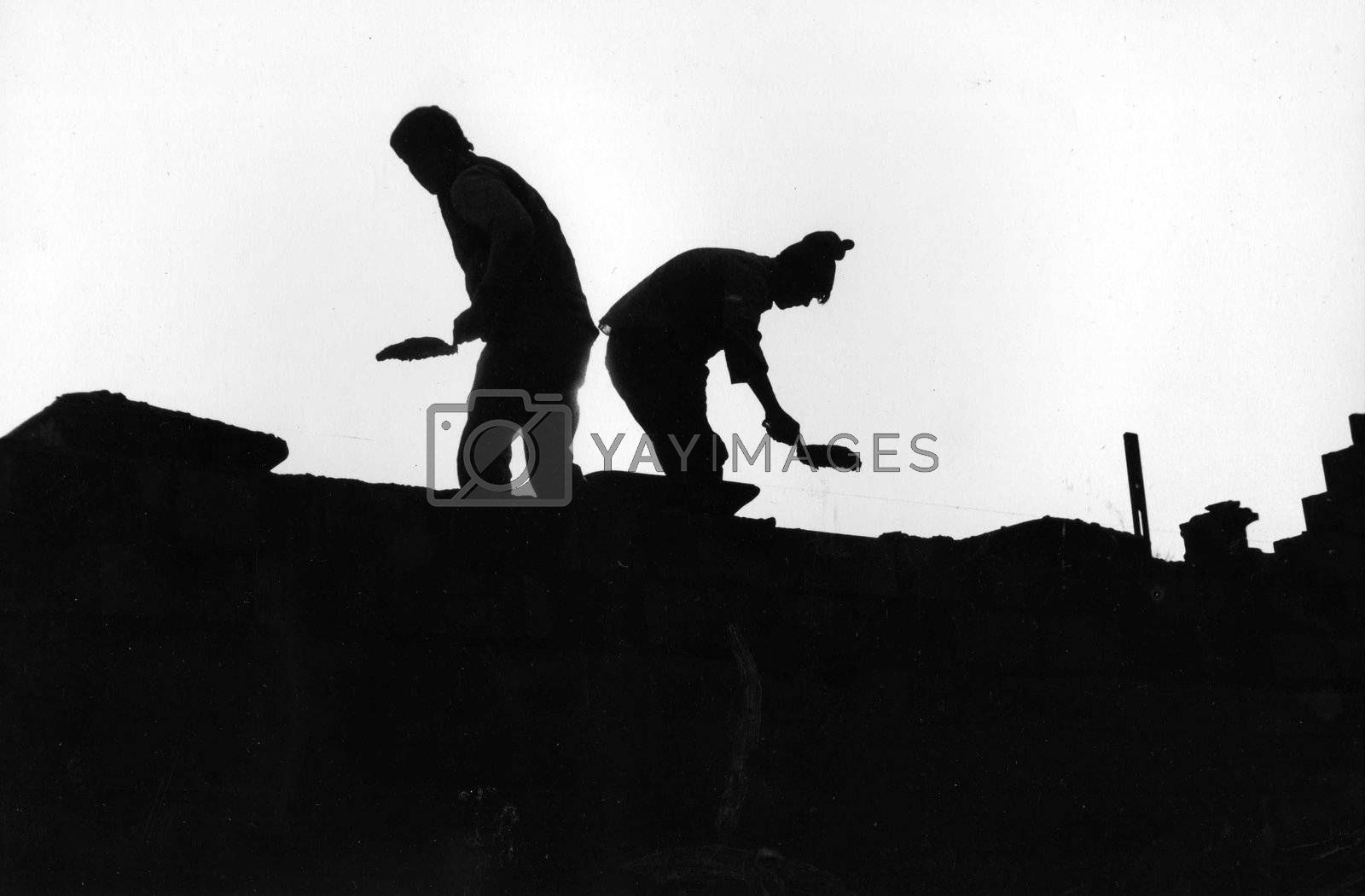 Two Masons working silhouettes against the sky by athomedad