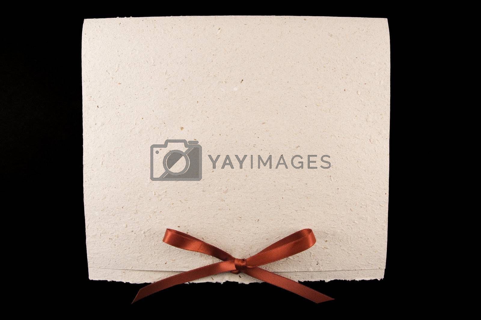 Close-up of a white parchment (diploma) with red ribbon on black background
