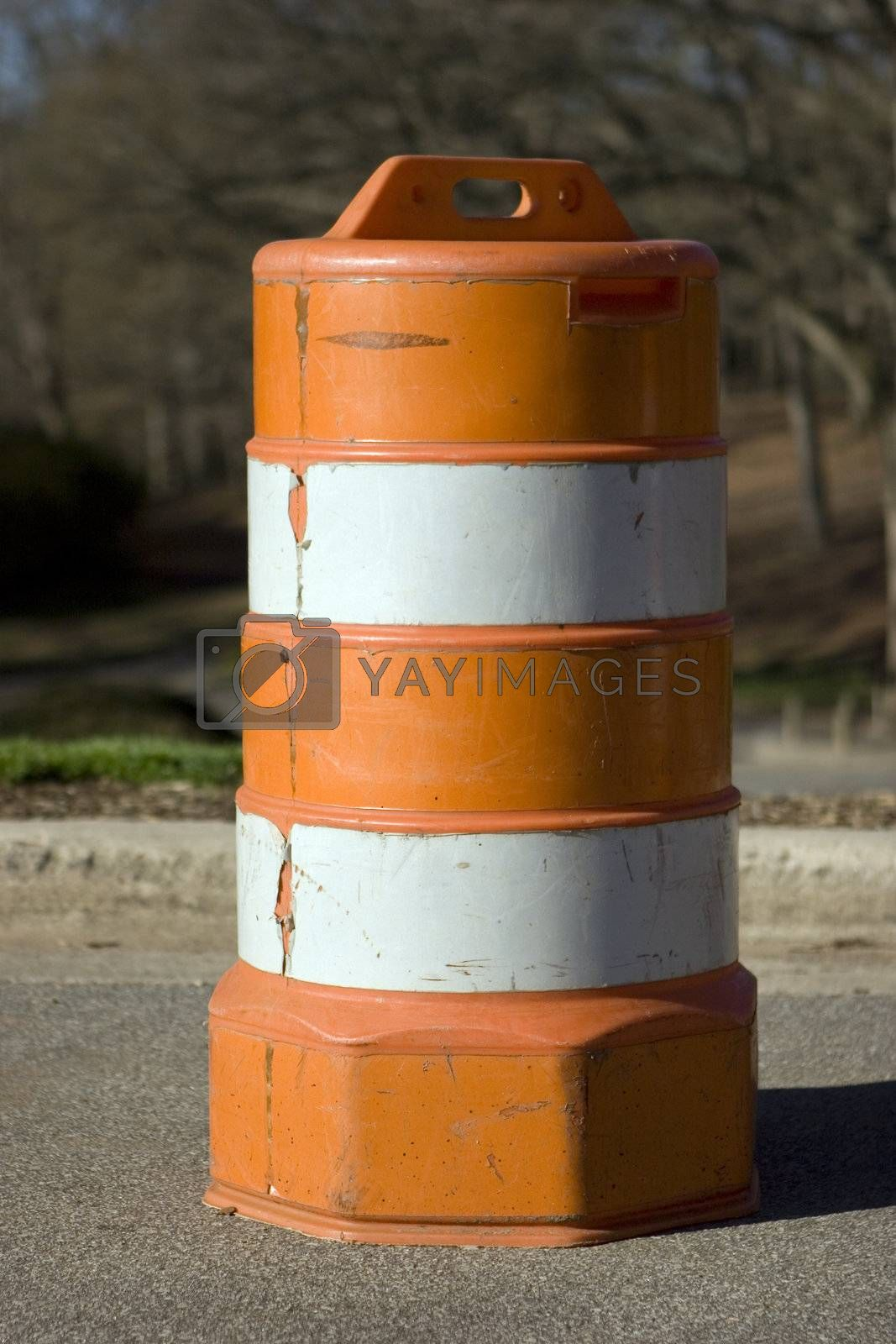 A traffic barrel on the side of the road.