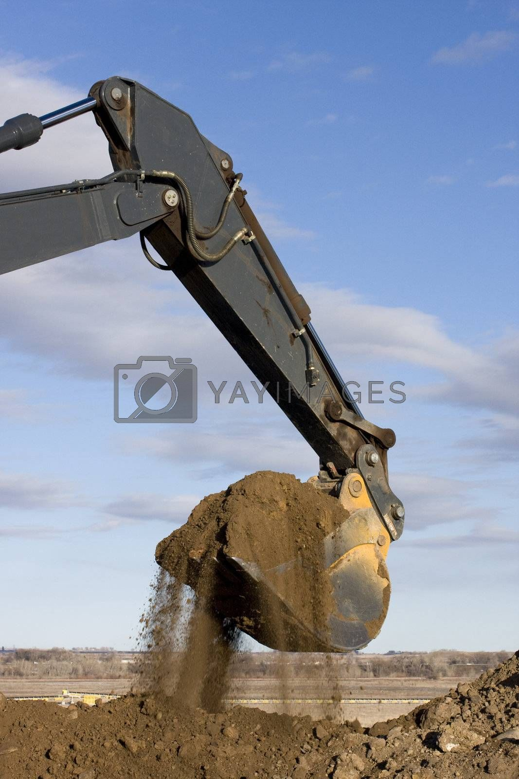 Excavator arm and scoop digging dirt at road construction by PixelsAway