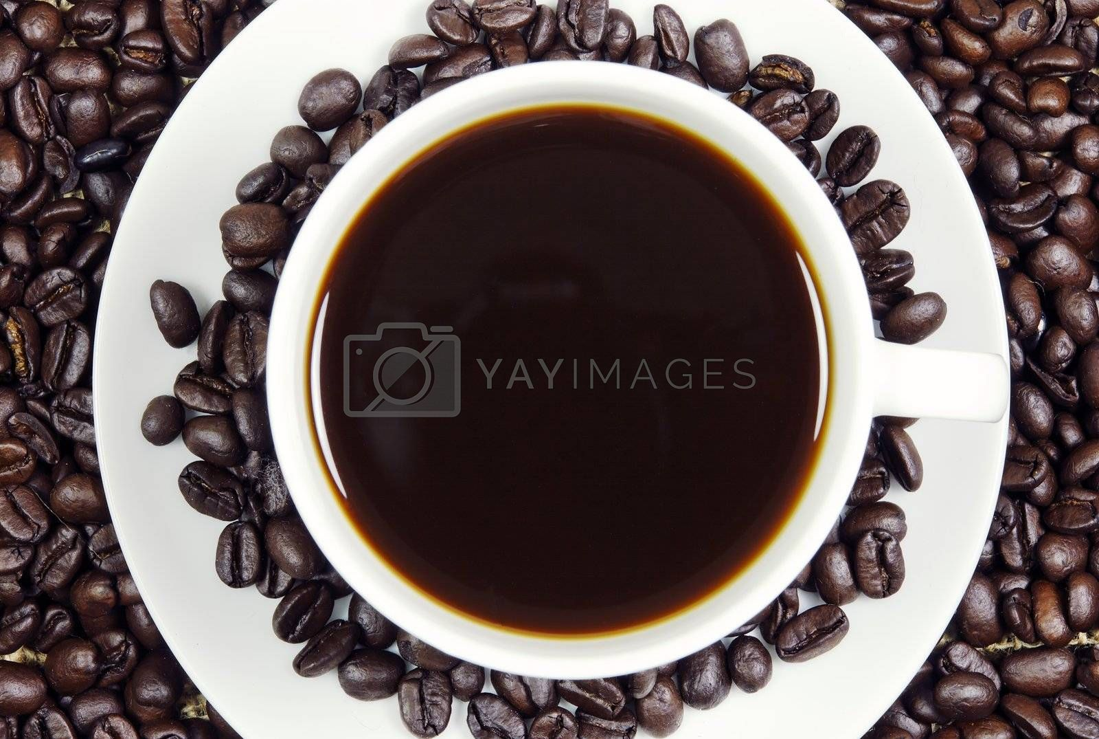 A cup of fresh black coffee surrouned by roasted coffee beans