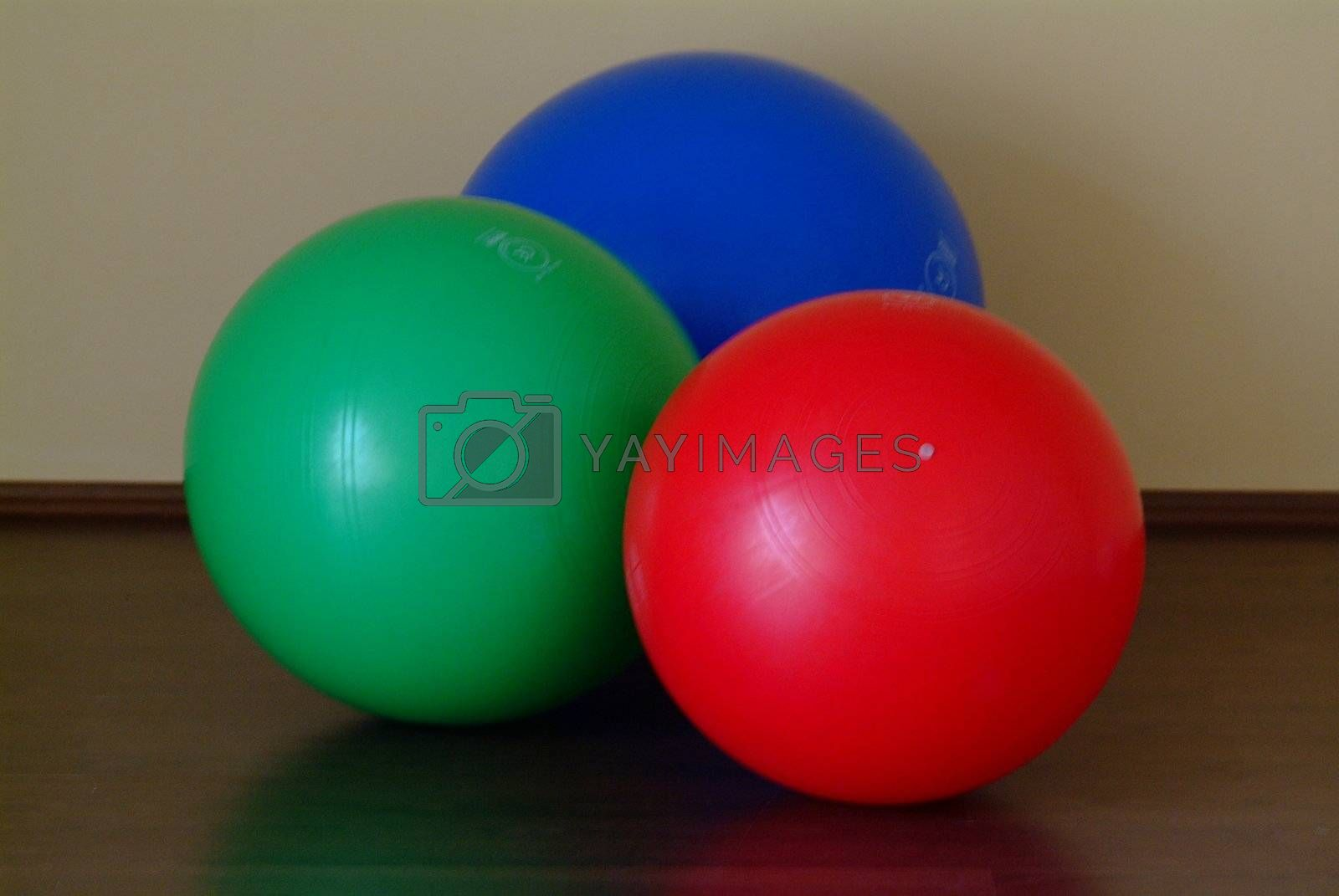 gym balls in blue, red and green on the floor