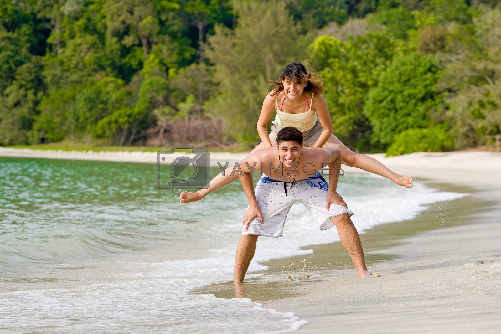 young woman and man playing leapfrog at the beach