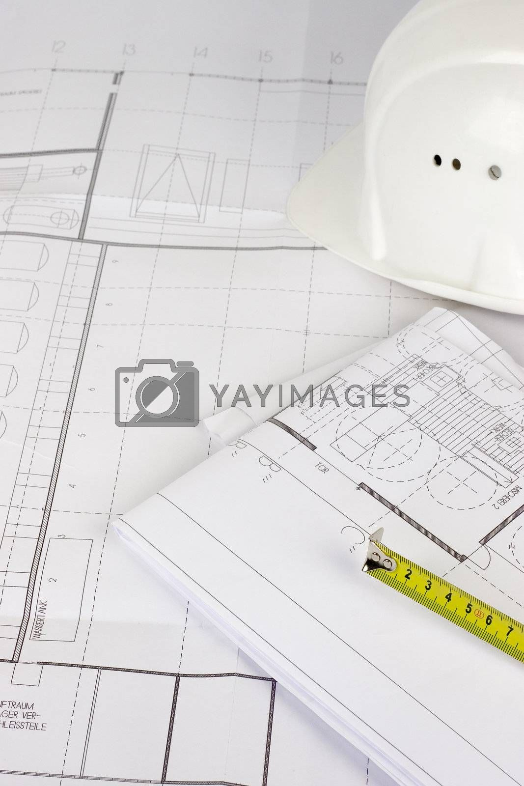 Hardhat and measuring tape lying on construction plans. Focus on the measuring tape.