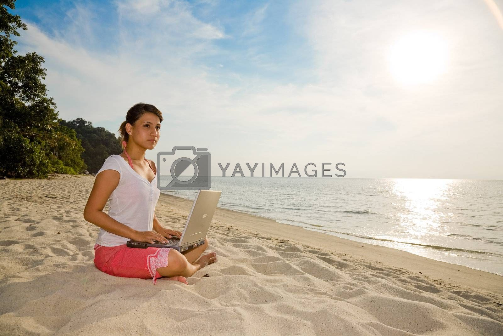 young woman working on her laptop on a beautiful beach during sunset