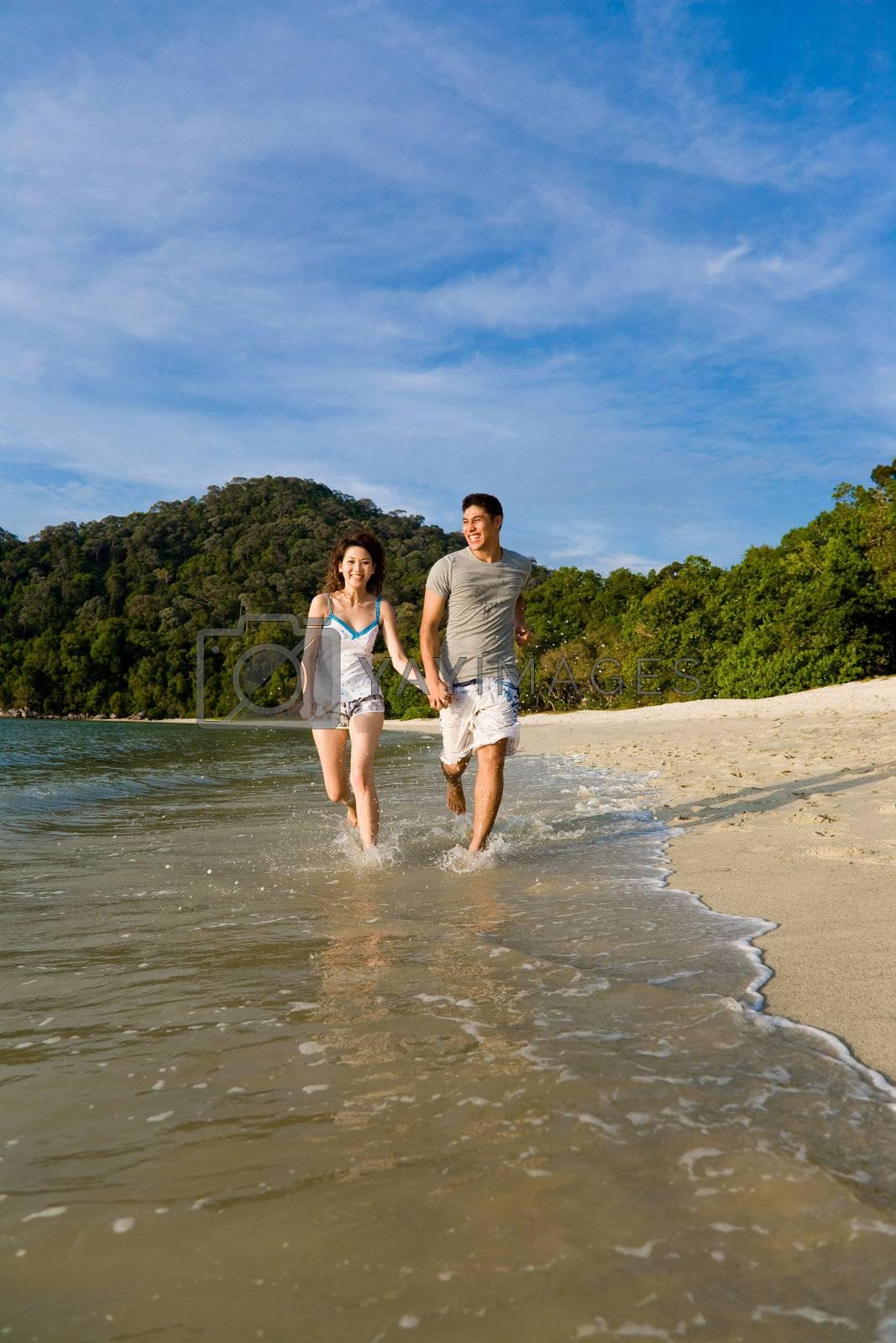loving couple running along the beach by eyedear