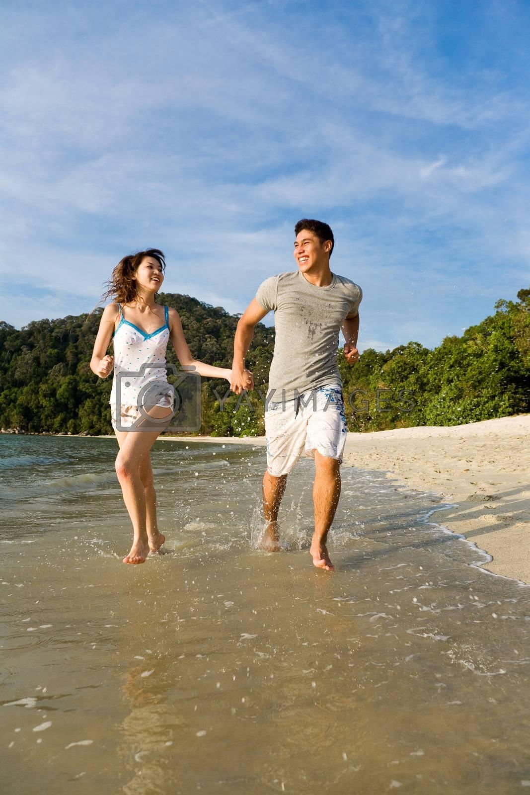 happy couple running along the beach by eyedear