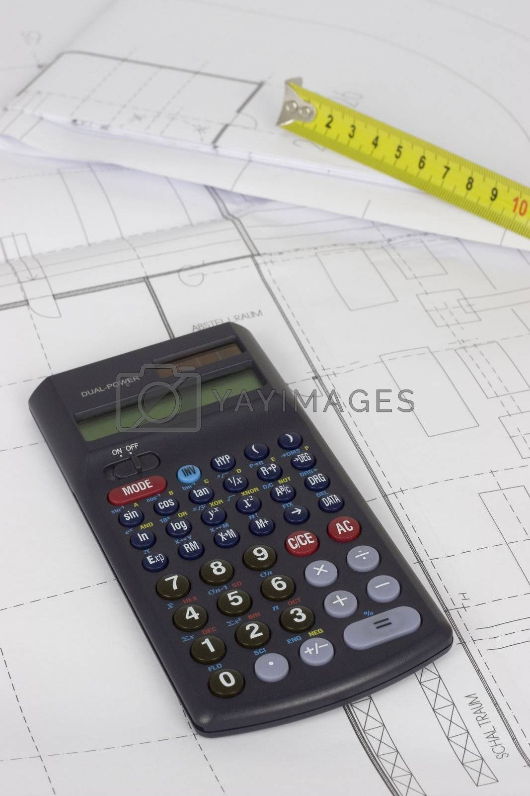 Yellow measuring tape and calculator lying on construction plans