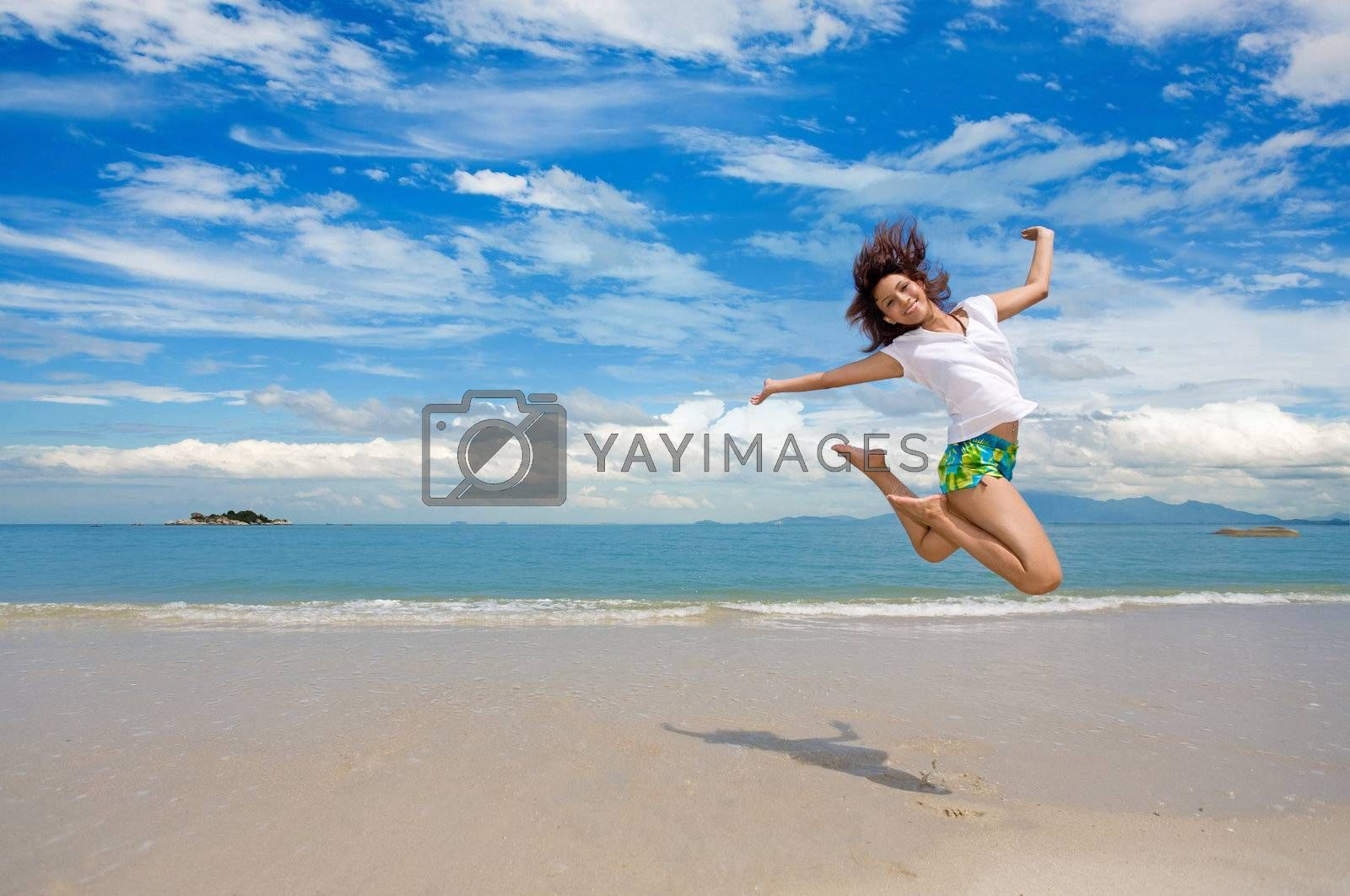 young beautiful girl jump gracefully at the beach