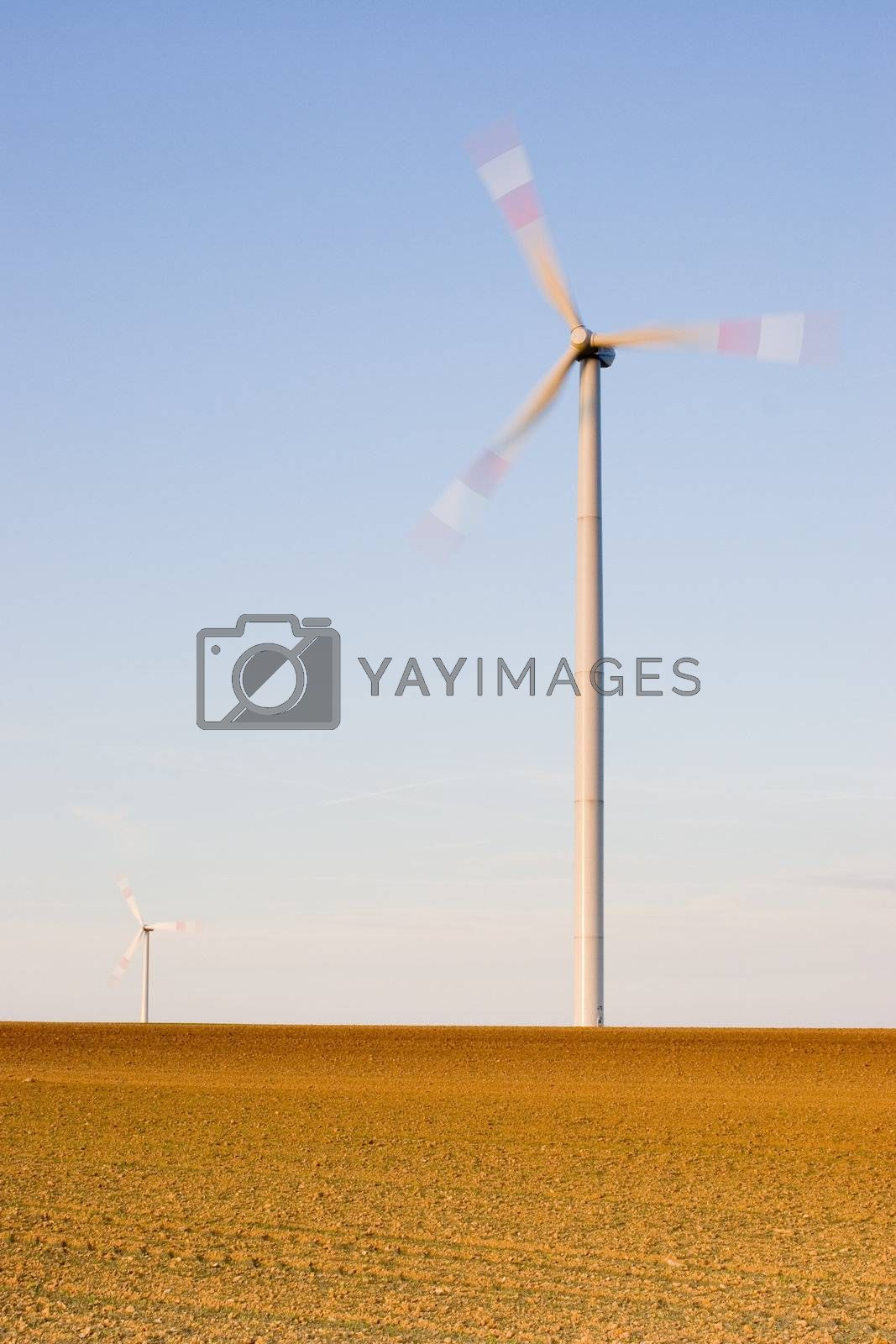 Two wind-turbine on a field at sunset. With long exposure time for motion blurred propellers of the wind-turbines.