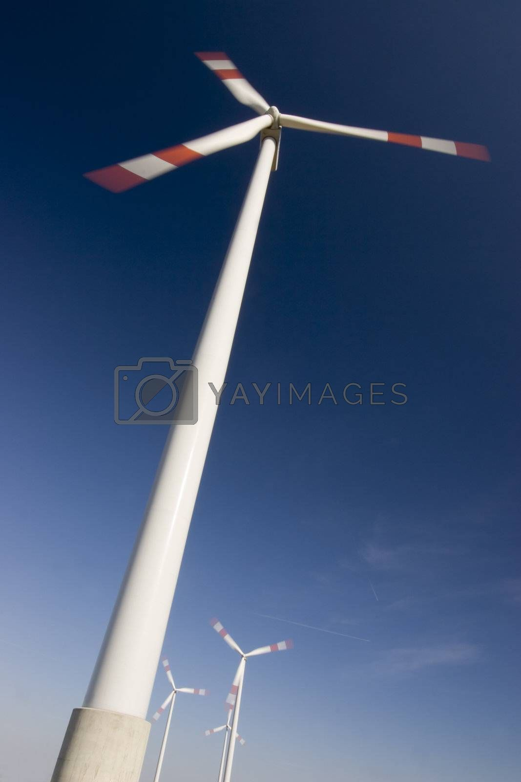 Rotating wind-engines against dark blue sky. Motion blurred propellers.