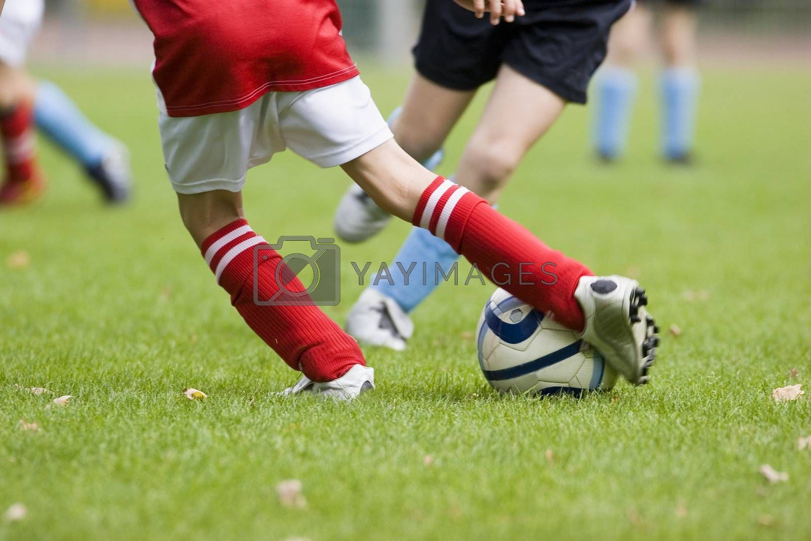 Detail of a football match - focus on the feet and the football