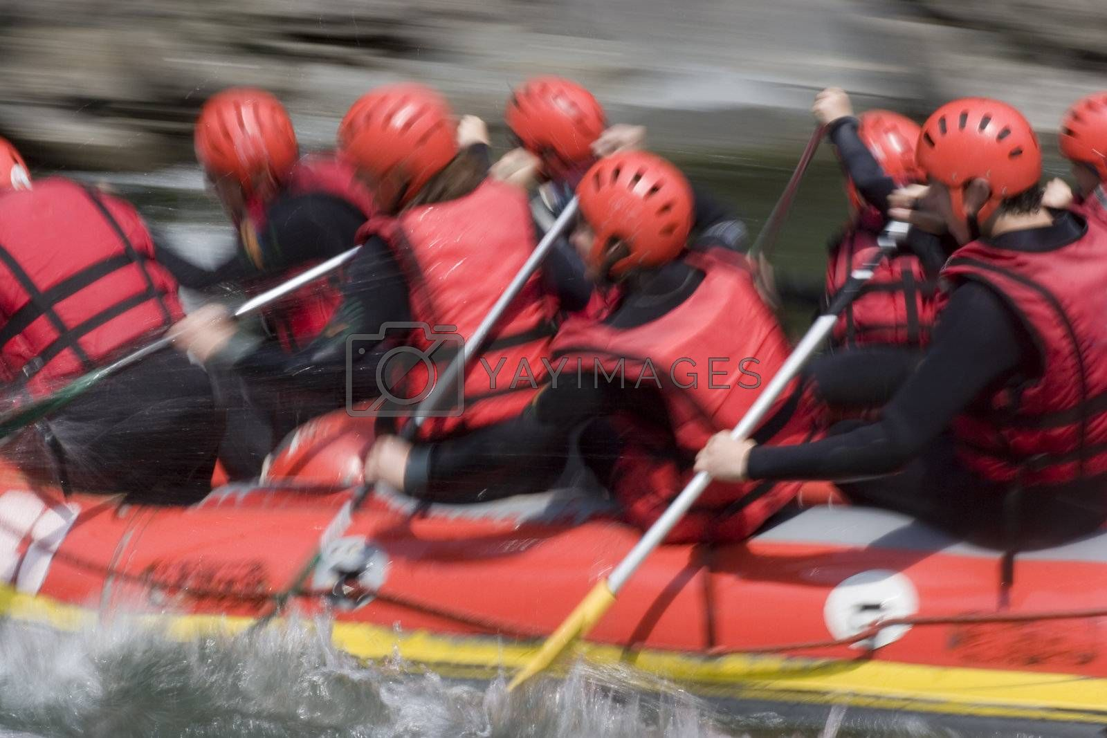 A red rafting team in action on whitewater. With tripod and long exposure time - motion blurred.
