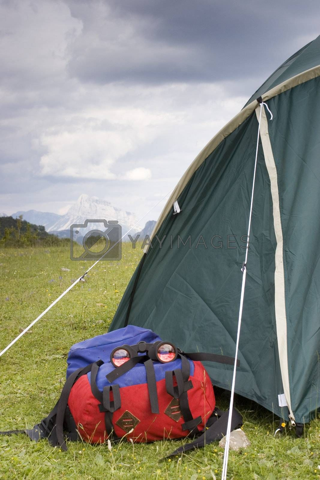 Tent, backpack and binoculars in front of a mountains scenery
