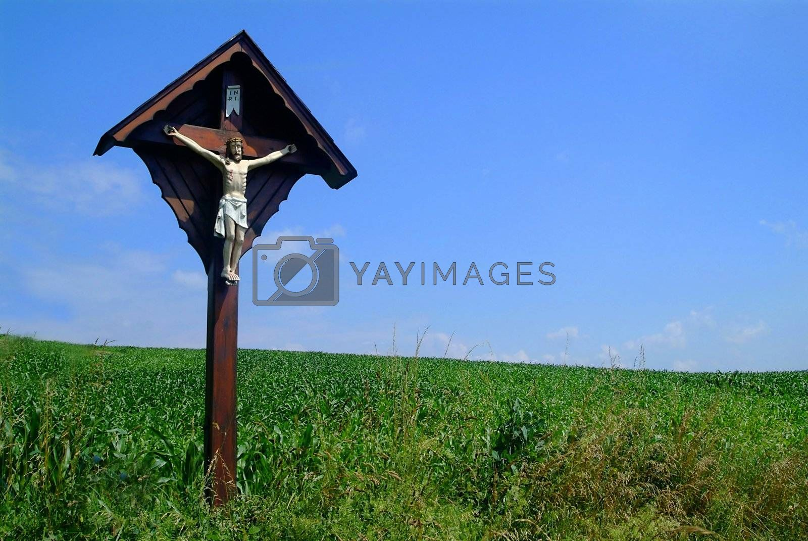 cross and jesus at meadow with blue sky