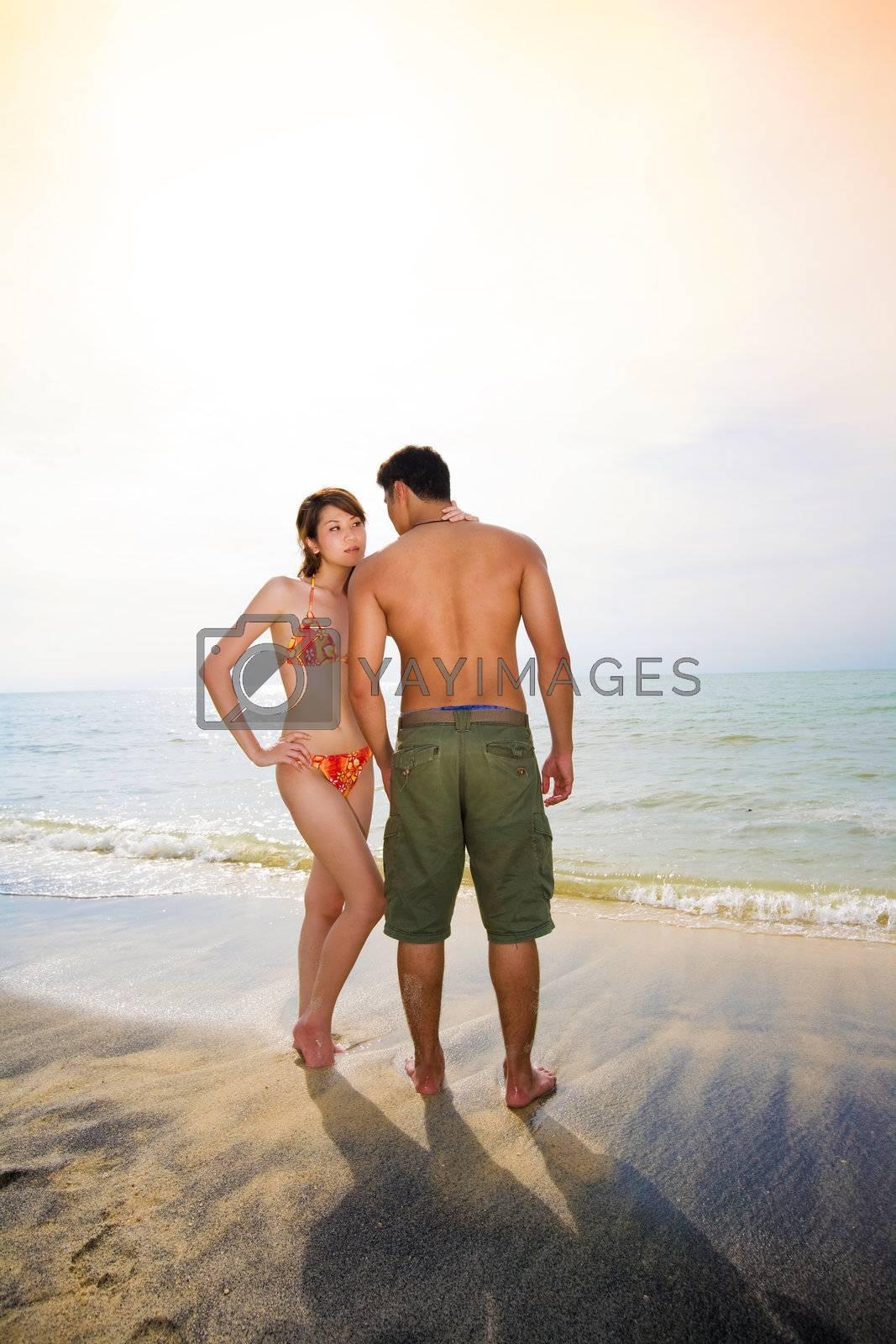 romantic couple on sunset beach by eyedear