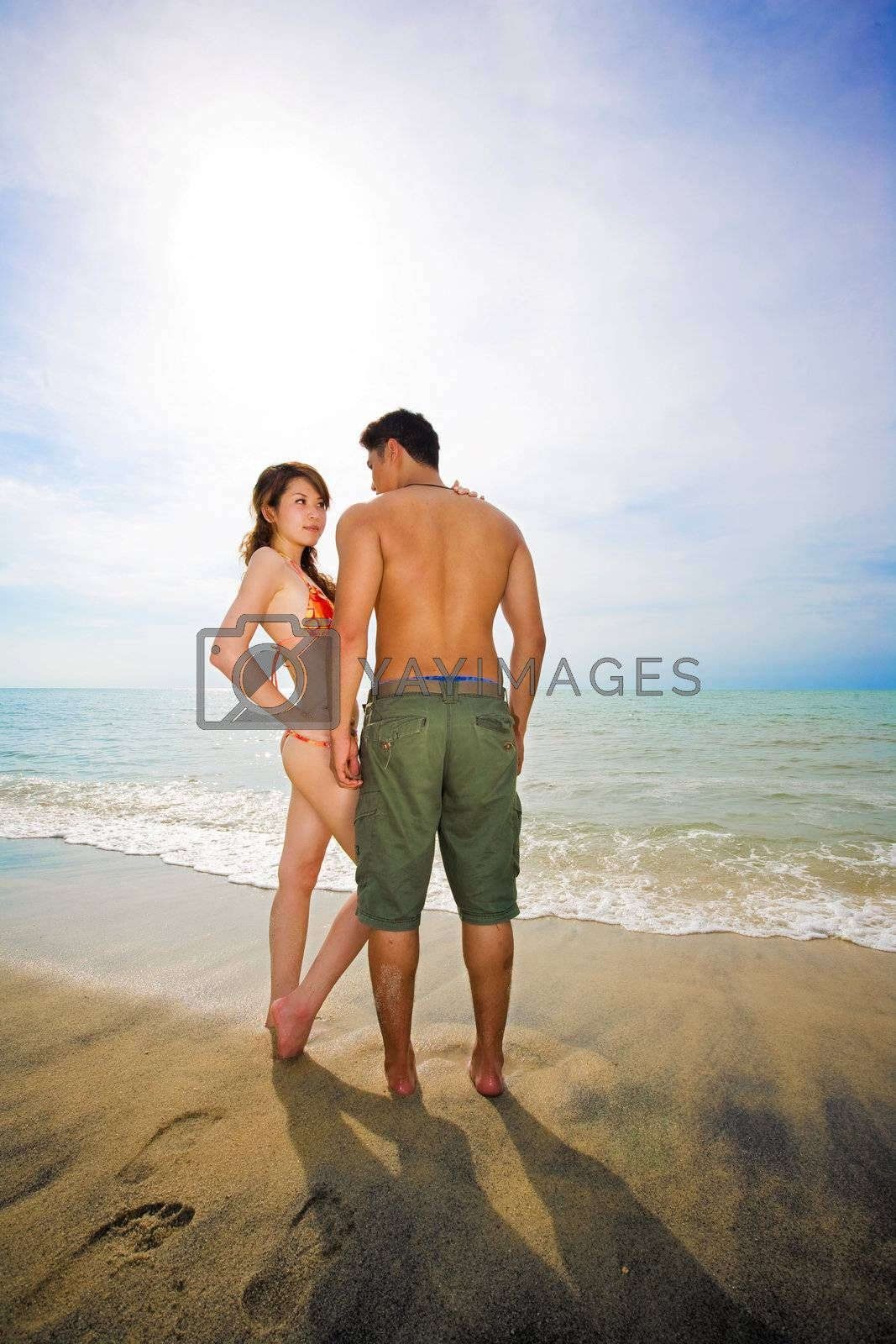 young couple enjoying romantic time by the beach