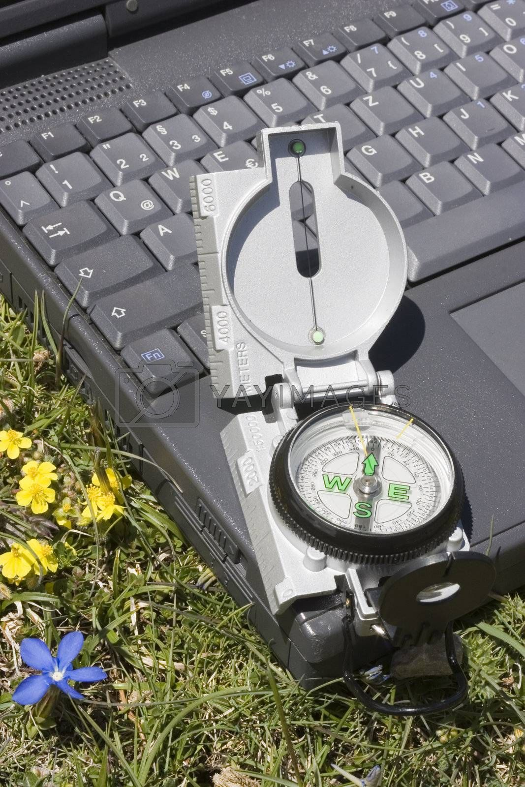 Compass lying on a laptop in a mountain meadow