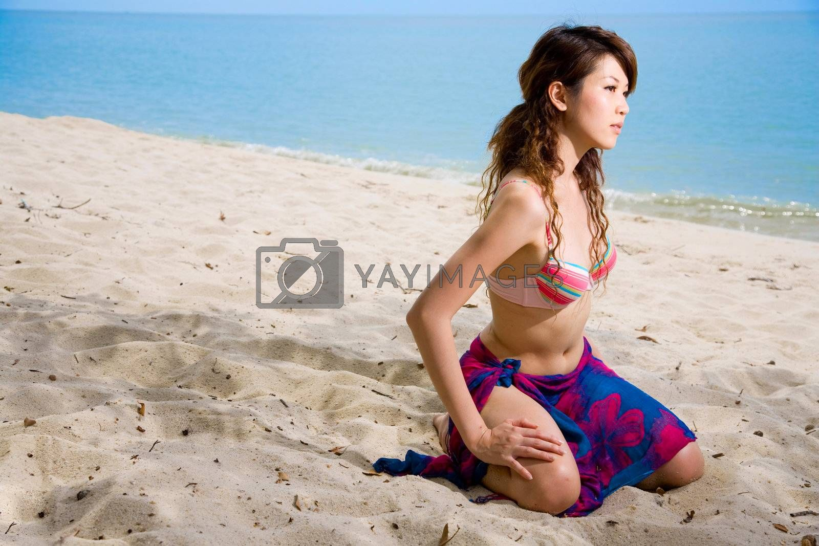 woman kneeling on the beach by eyedear
