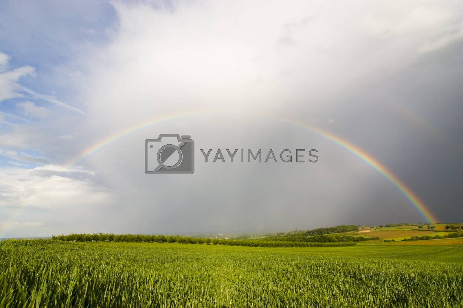 Complete rainbow over a rural landscape on a stormy day