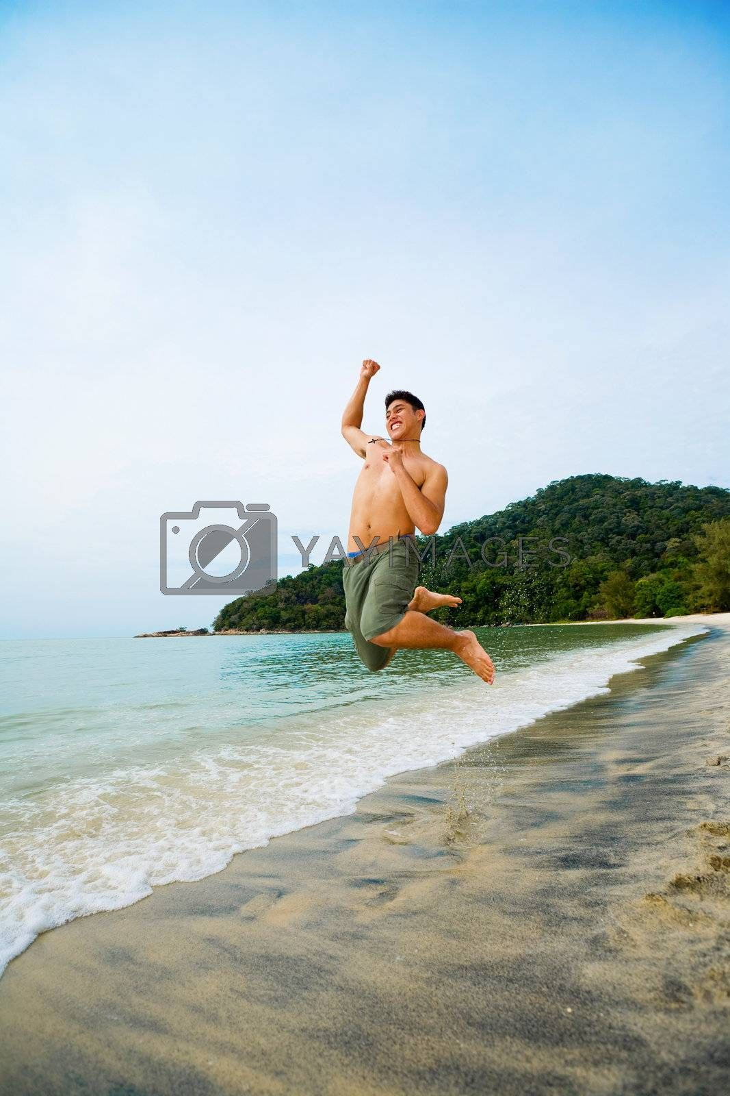 man jumping high up happily on the beach