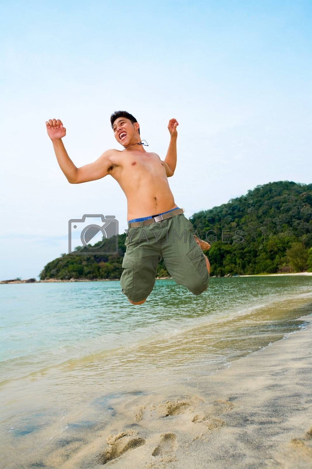 man jumping in excitement on the beach