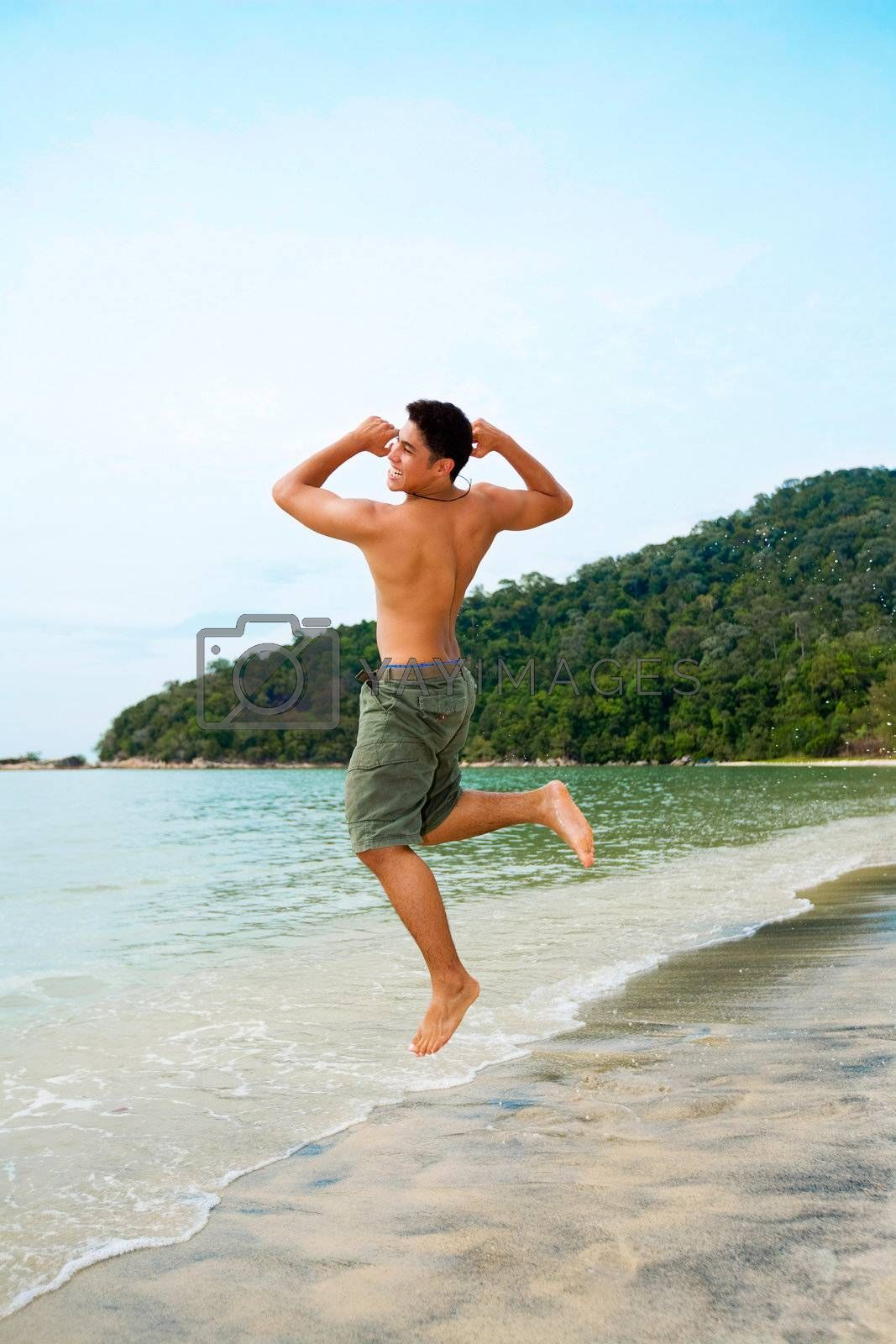 man jump up happily by the beach with excitement after successfully reach his goal