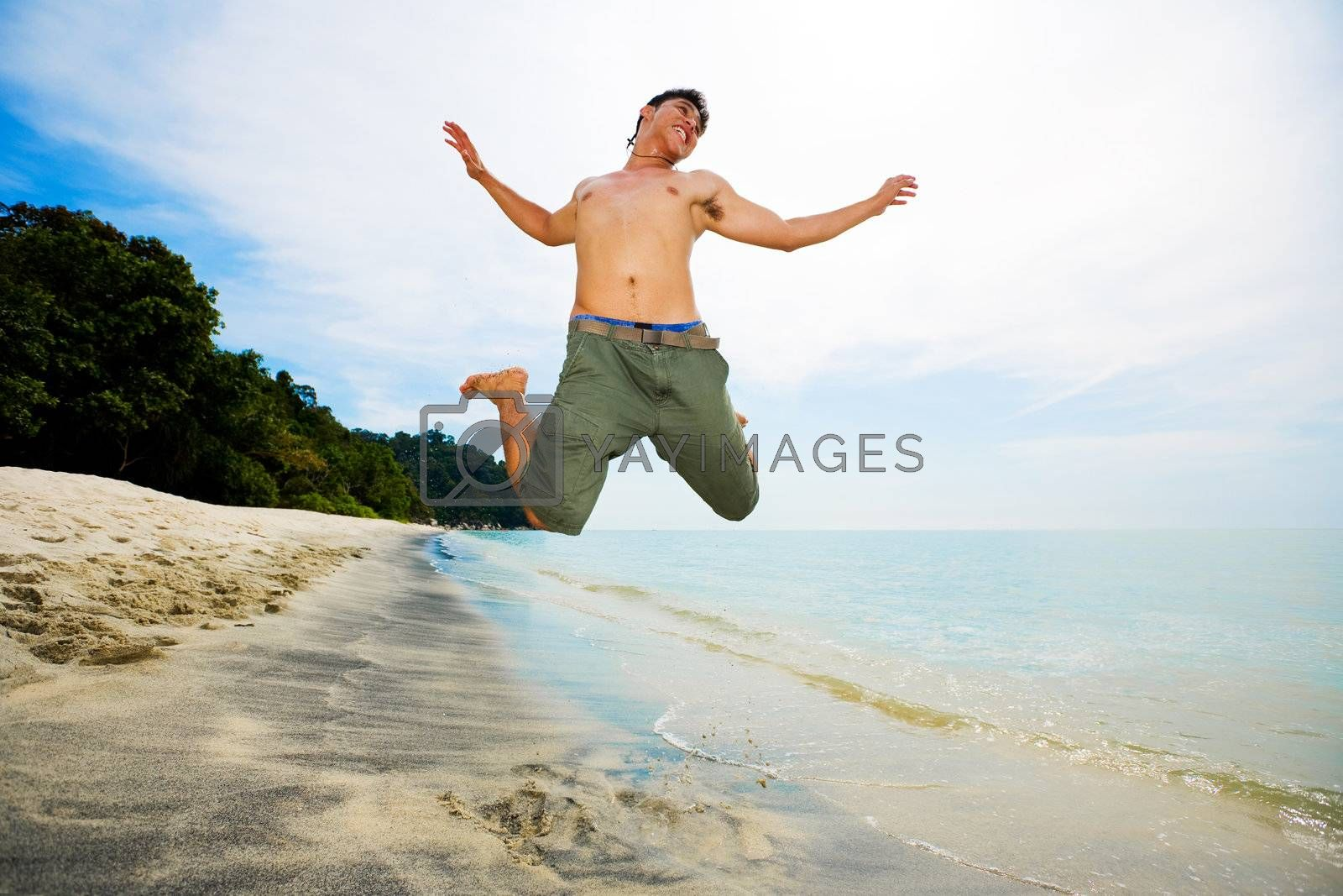 happy man jumping in excitement on the beach